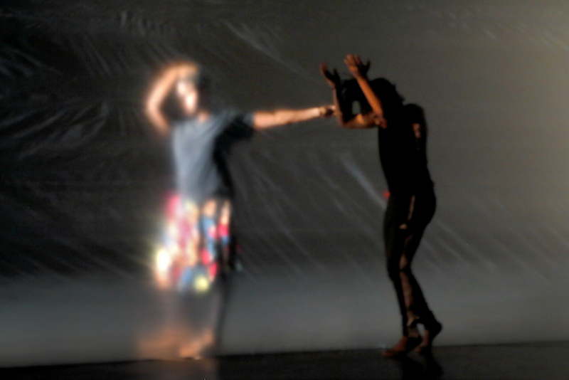 A woman dances behind a plastic sheet and another dances in front of it