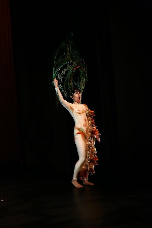 Jules Skloot wears a unitard with feathers trailing down the midline to the foot. A headpiece made of grass and plants sits atop his head.