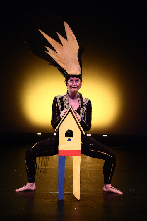 Lindsay Reuter assumes a deep second position. A small prop that looks like a birdhouse sits in front of her. She hears a headpiece with looks like painted yellow hair sticking straight up.