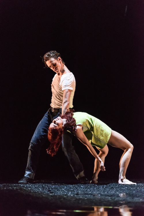 Polunin in a white t shirt holds Polunin by her neck as she does a back bend