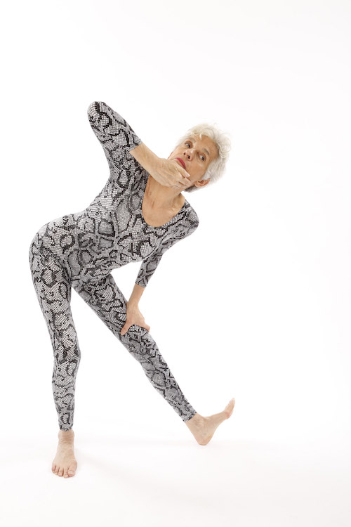 Wendy Osserman in a snakeskin unitard lunges while one hand rests above her left knee and the other grazes her chin