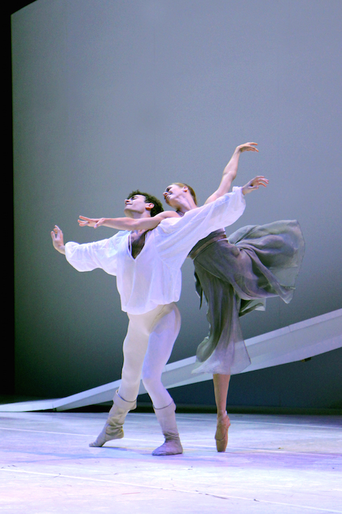 Lesley, in an arabesque on pointe with her right arm supported by Jerome's shoulder