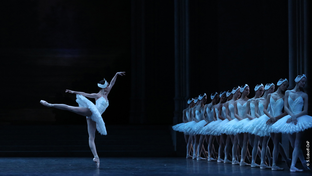 Odette performs an arabesque in front of the swan corps