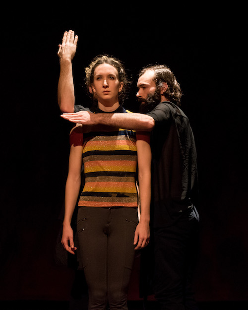 A male dancer stands next to a female dancer. His arms surround her shoulder making a ninety degree angle. The female dancer dressed in a striped tank stares out to the audience