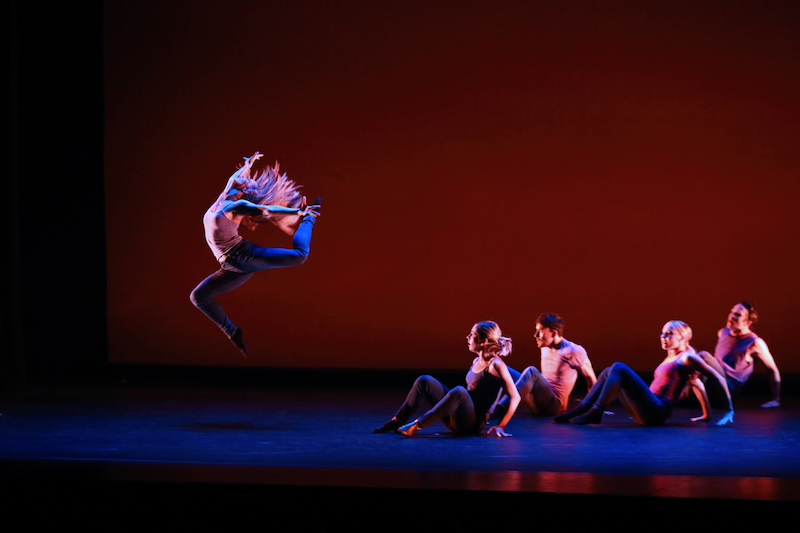 Four dancers sit and watch another dancer jump high into the air. Both of her legs are bent and her head tilts to the ceiling. Her blonde hair cascades around her.