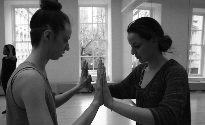 Two dancers face one another and connect their palms