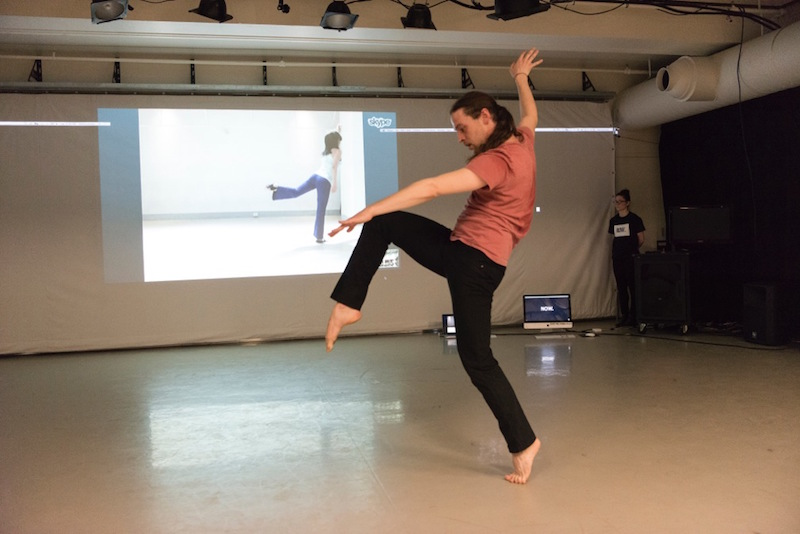 A man balances on one leg in the studio with his other leg hovering in front of him. His counterpart on video also balances on one leg but her other leg is behind her