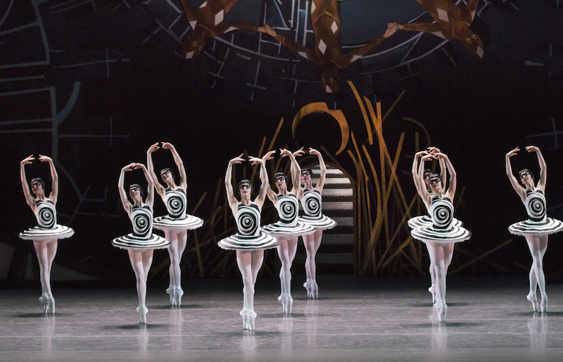 Nine ballerinas in black and white tutus that have a back swirling op art line on the front. All of the dancers don black page boy wigs and black glasses over their eyes