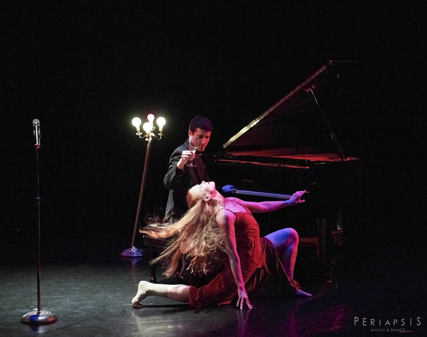 A man at a piano offers a lunging woman wine