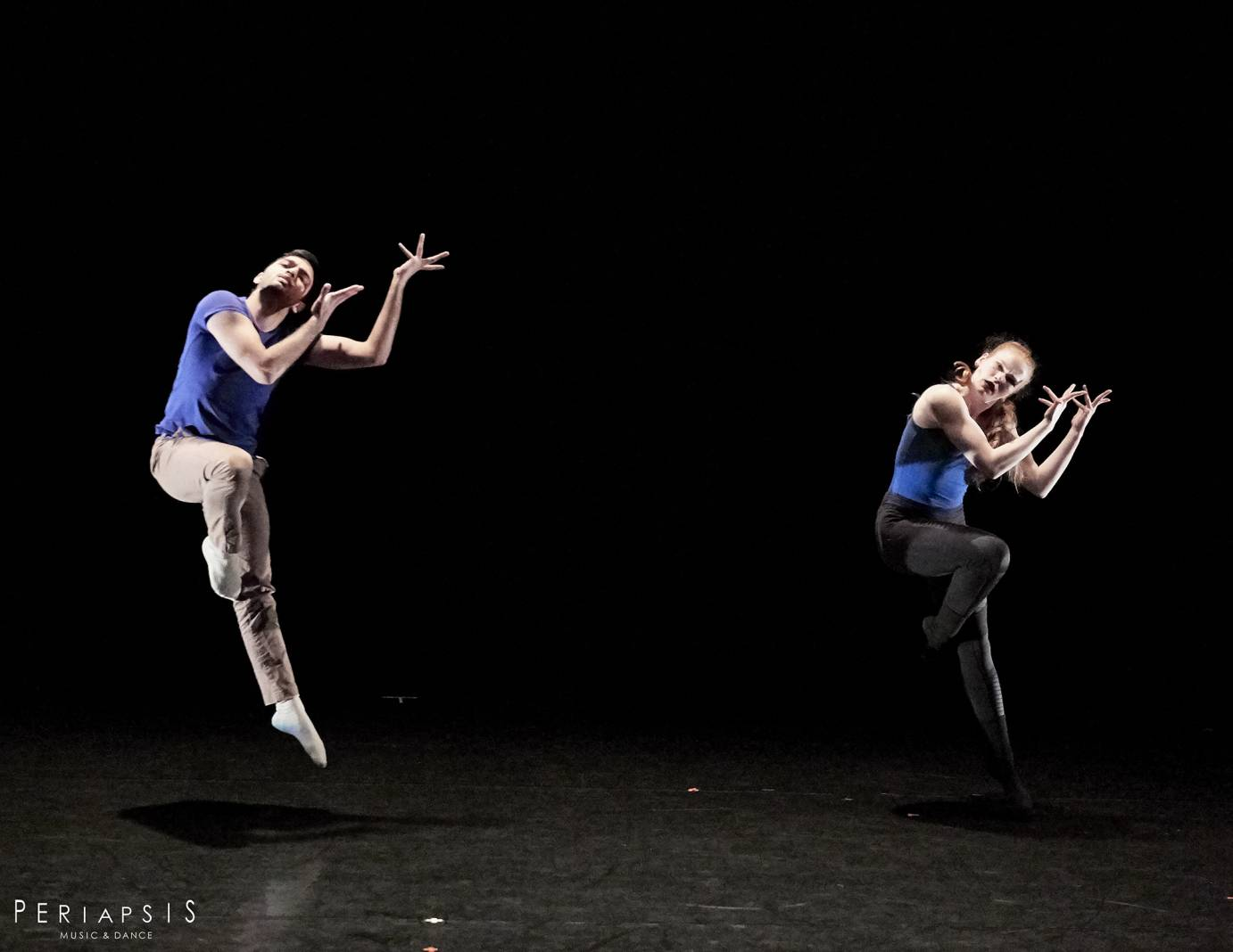 A man and a woman in blue tops jump with one leg touching their knee and splayed fingers