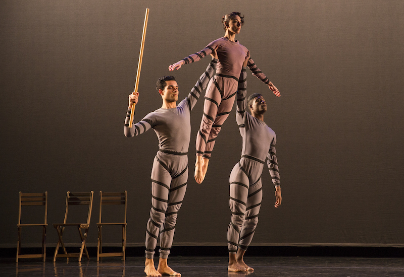 Two dancers lift a dancer between them over their head. Three wooden chairs are in the background. One dancer holds a wooden staff.