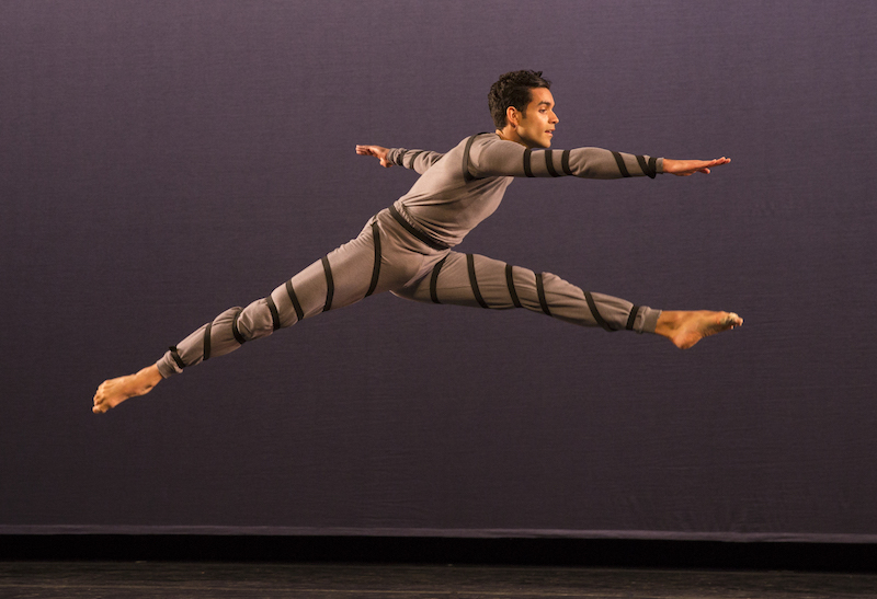 A dancer leaps into the air as if he's jumping over a fence.