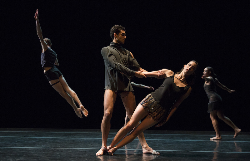 In the foreground, one dancer leans and is held by the arm by another artist. A dancer, with their back facing the audience leaps high into the air.