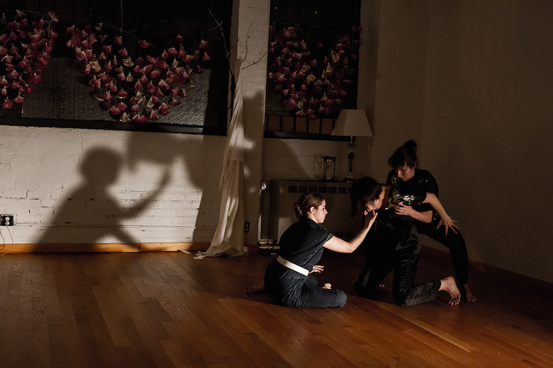 Three dancers dressed in black intertwine their bodies in the shadows