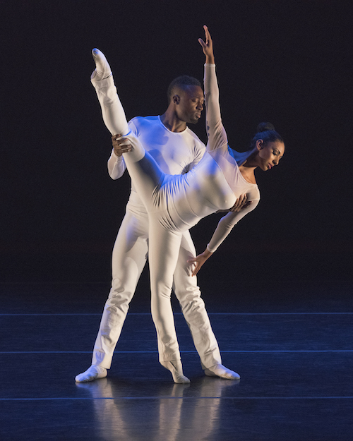Two dancers in white. One dancer extends her leg high in the air as her torso drips to the side. Her partner stands behind her and helps her balance.
