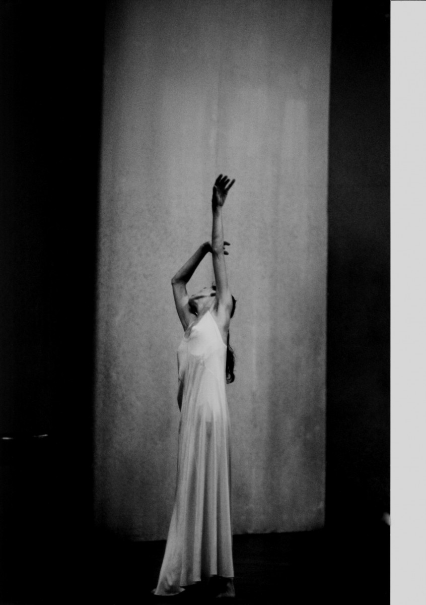 Pina Bausch in a long silk dress lifts her arms above her head.