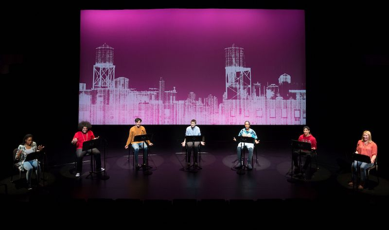 Students sit in chairs reading from the Undesirable element scripts in front of them that are placed on music stands. A magenta colored projection of a city skyline is displayed behind them.