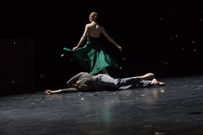 A woman faces a way from the camera wearing a silk emerald green gown while a man lays on the floor.