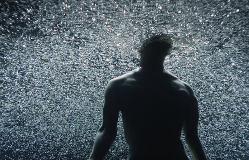 A shirtless man faces a sparkly background
