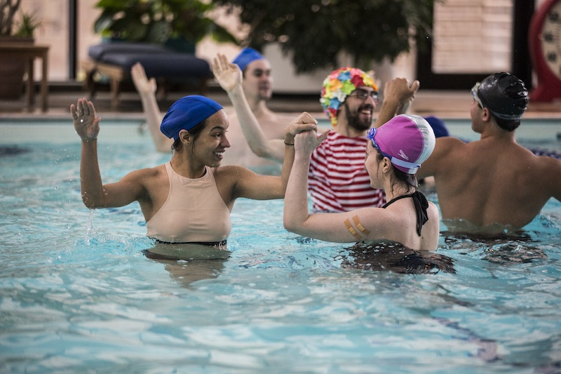 Performers in bath caps and suits pair off in the pool. They reach clasp their partners hand as their stand in the shallow end.