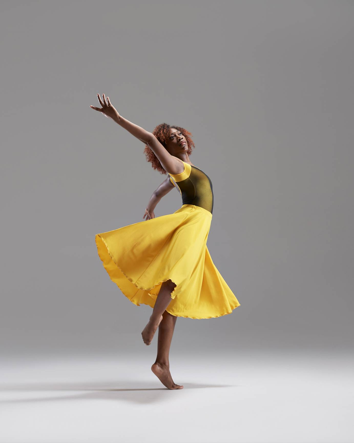 A young woman in a yellow dress swoops in an elegant pose
