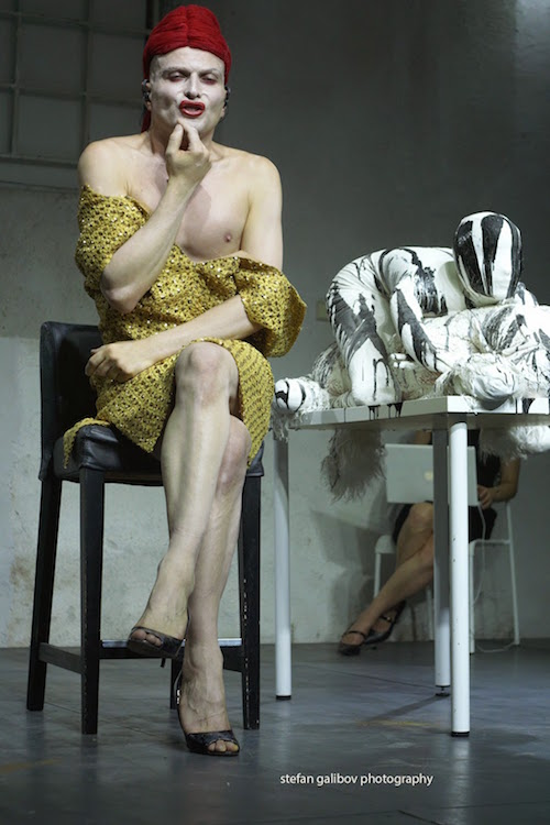 Ivo Dimchev sits in a chair miming putting on lipstick, wearing a crocheted dress