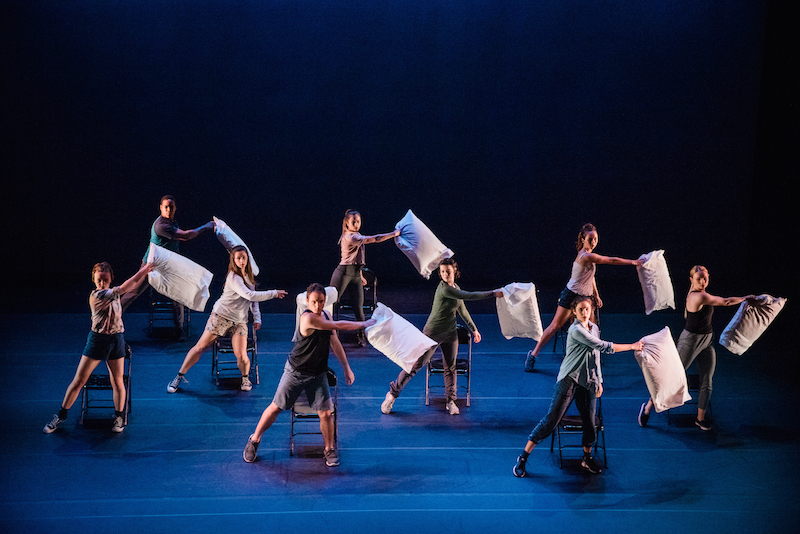 The ensemble in street clothees each hold a pillow in their right hands and stand in front of a folding chair