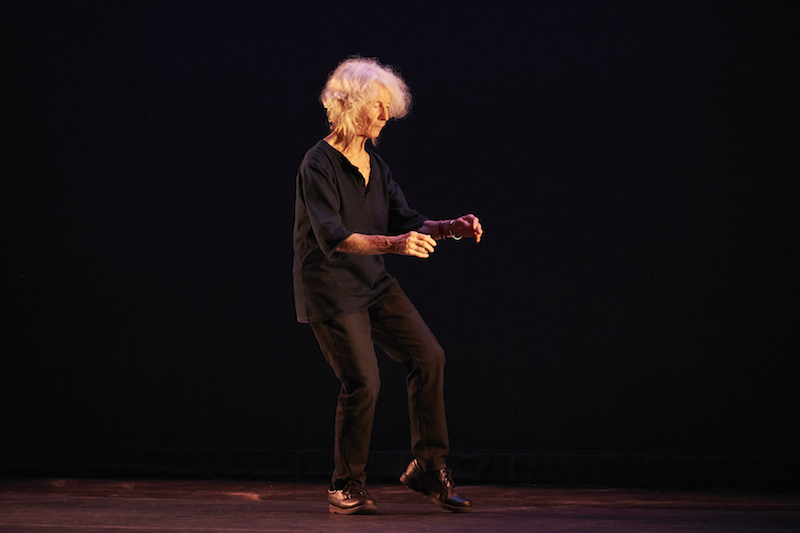Simone Forti wears black slacks and shirt as she stands on one leg. Her two arms are in front of her.