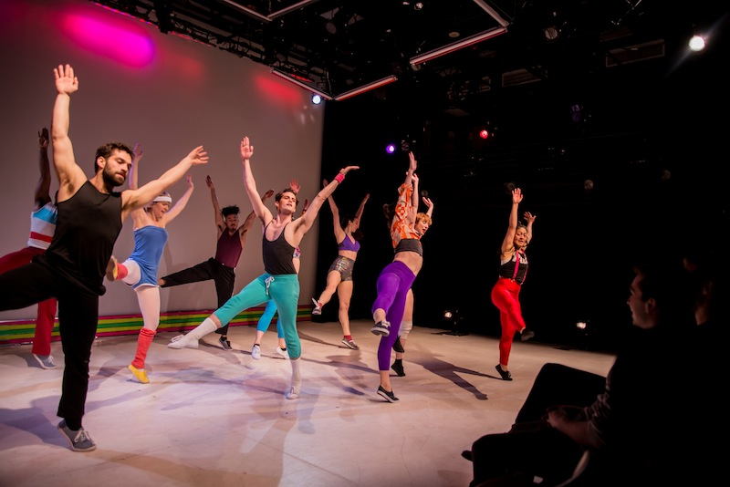 Dancers in colorful 80s style rehearsal clothes with their arms above their heads and right legs extended into the air