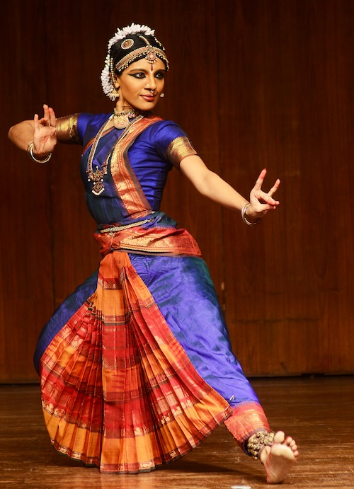 Aparna in bright purple traditional classical Indian dance garb. Her left foot is flexed and her fingers are splayed