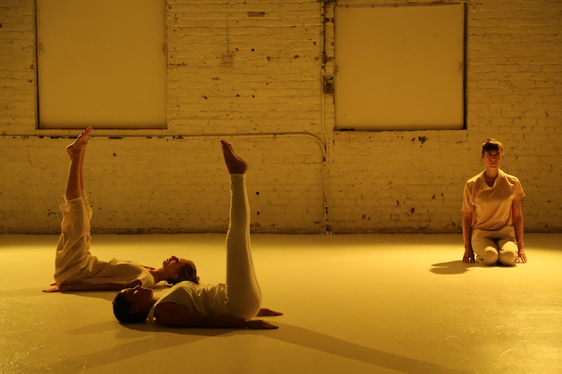 Two women lay on their backs with their legs raised to the ceiling. A third woman sits on her knees under a yellow soft glow.