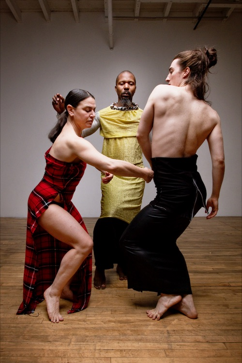 Three dancers in body-hugging long sheath dresses or skirts. One wears a red plaid strapless dress that has a slit up its side. Another wears a gold tunic.