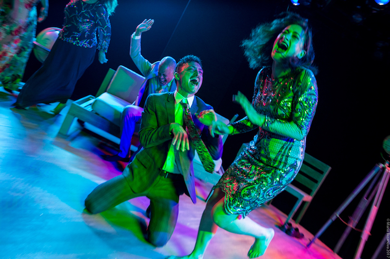 The performers in mid cackle. One, in a plaid suit sits on his knees and tilts his head back, another sits on the couch about to slap his knee and women with her mouth agape