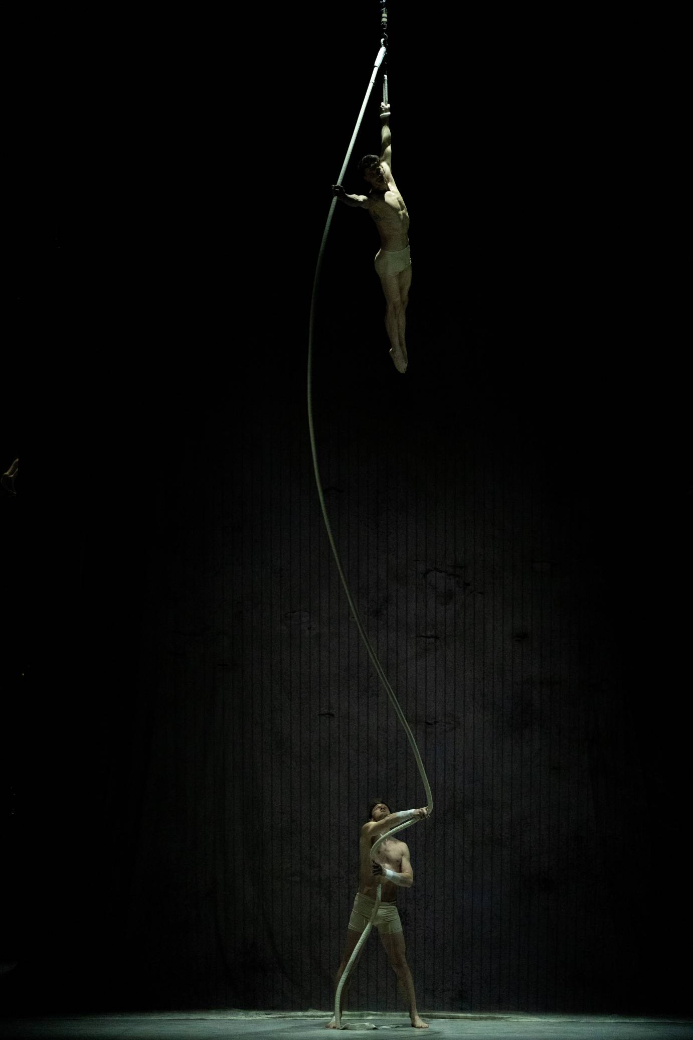 One man stands on a trapeze while another stands below him