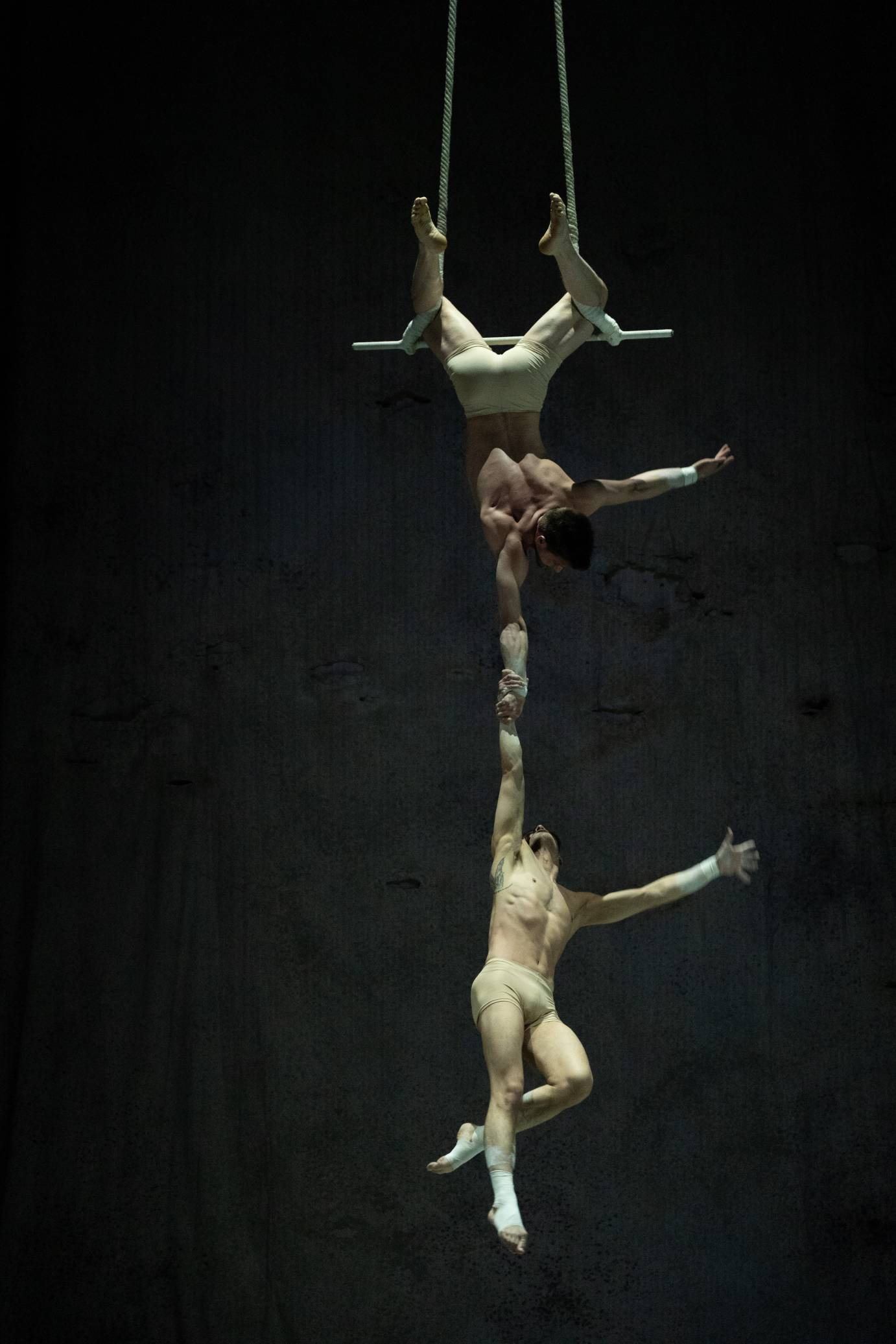 One man hangs from a trapeze holding another man with one hand