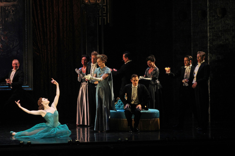 The company in evening wear surrounds Sara Mearns as Victoria Page who is sitting ion the grounds with her arms outstretched. She wears an emerald dress.