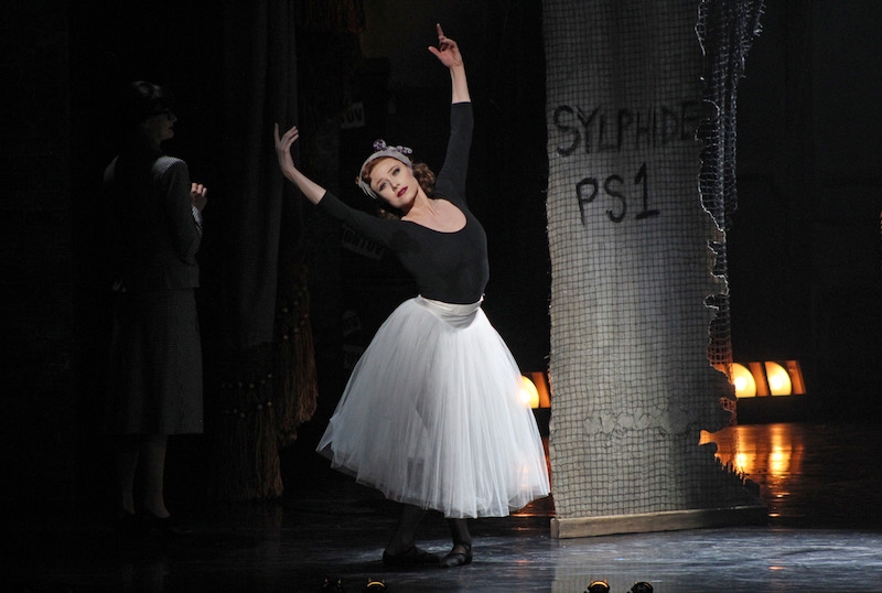 Sara Mearns as Victoria Page wears a black leotard and romantic era white tutu. She stands in a classical ballet post - fifth position with the legs and feet.