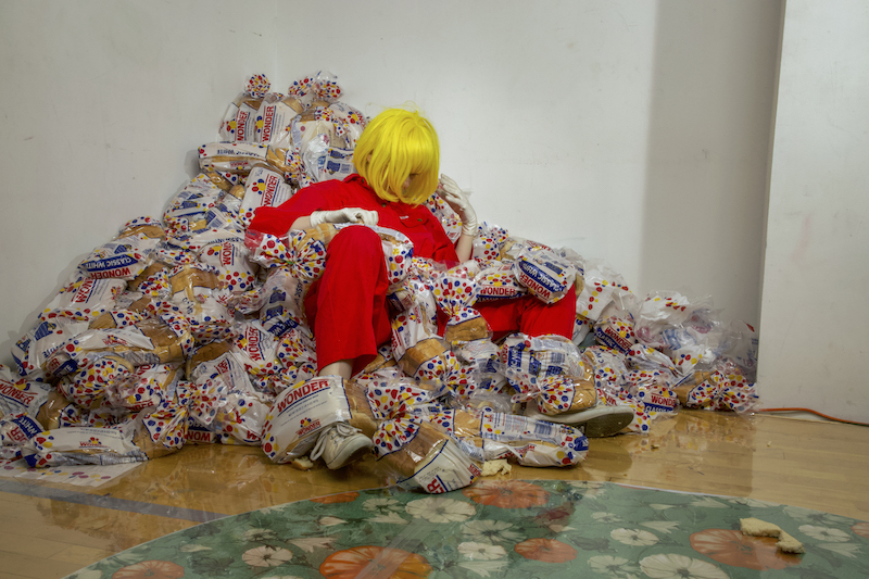 A performer, in a bright yellow wig and red jumpsuit, sits in a pile of Wonder Bread.