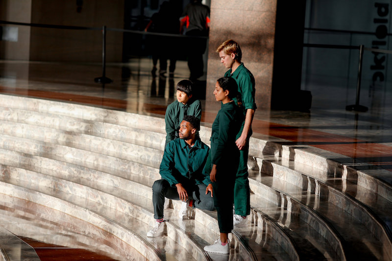 Four dancers, in evergreen jumpsuits, sit on the marble steps of Brookfield Place.