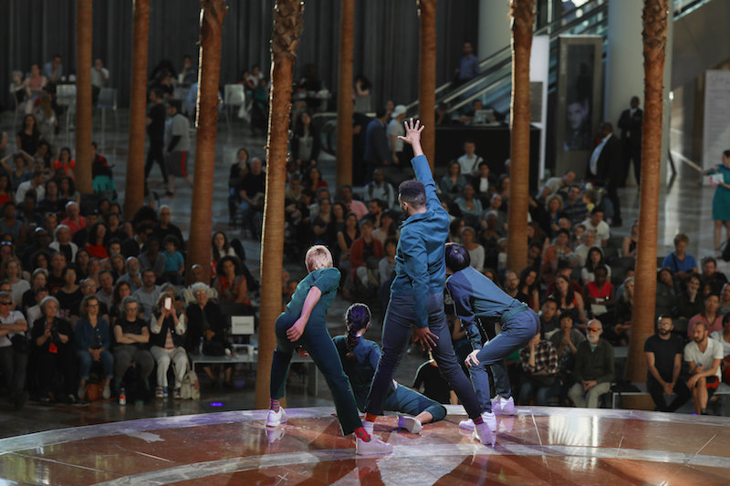 Four performers in everygreen-colored jumpsuits pose and look down at the audience.