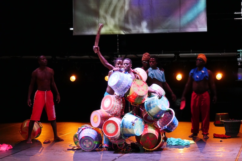 Colorful baskets are arranged in a shoulder high mound as male performers interact behind it