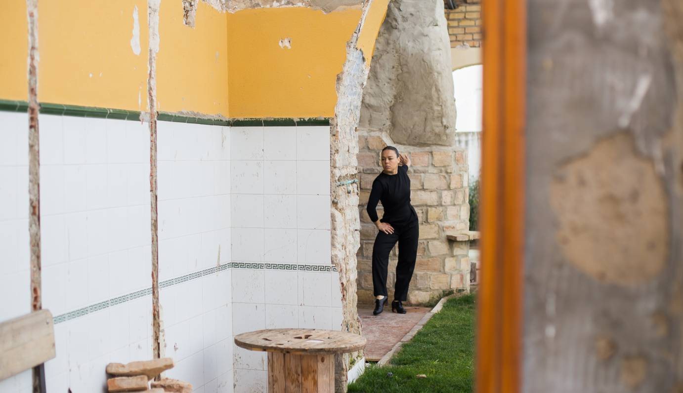 Rocio Molina presses a hand against a stone door jamb