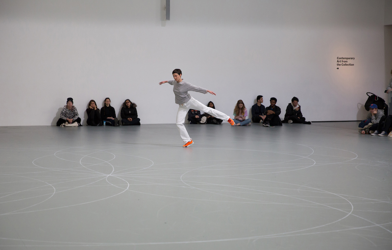 A dancer in white pants, a grey top and orange sneakers hovers on one foot. Her other leg is stretched behind her parallel to the floor. People are seated against the wall and watch.