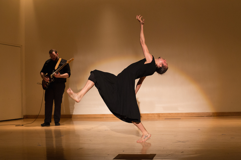 A guitarist plays in the background while a soloist in a black tunic arches his back. His leg hovers in the air and flexes at the ankle.