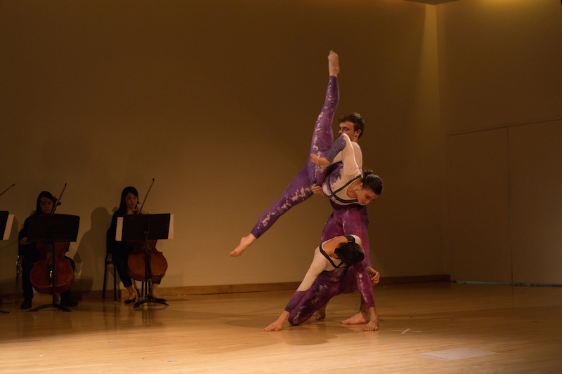A man lifts a woman in the air as she extends into a penchee arabesque position. Another woman kneels in front of the couple. A group of cellists are playing in the background.