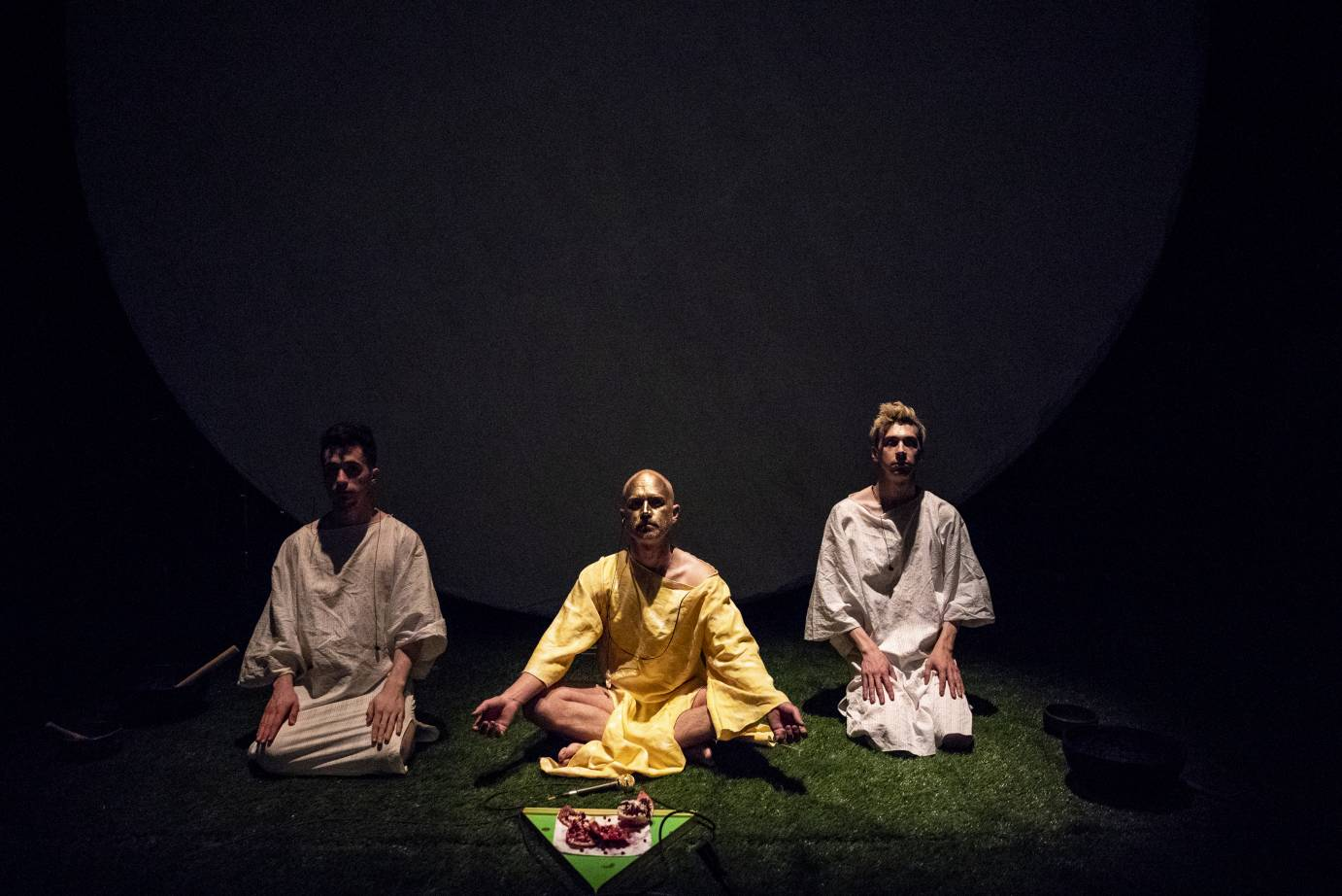 Three individuals sit like yogis behind a microphone and bowl of pomegranates