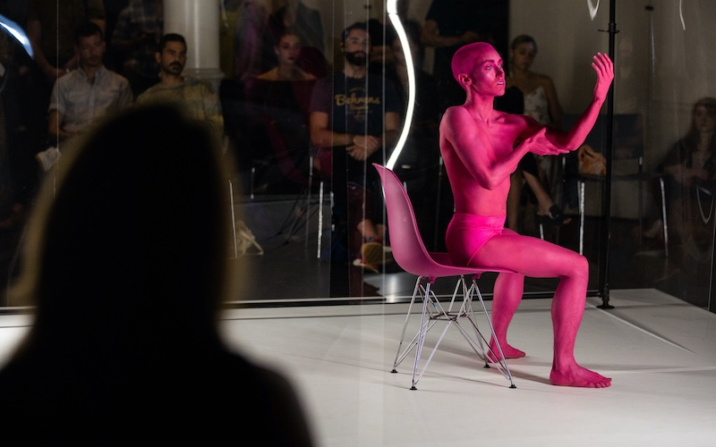 Dancer Molly Griffin sits in a hot pink office chair that resembles the shade of clay paint her body is covered in. She hold one arm out at a ninety degree angle. She holds her raised arm with her other hand by her bicep. Audience members watch behind clear plexi-glass.