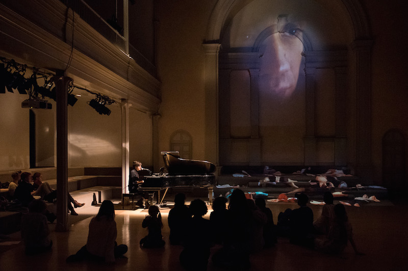 Morgan Bassichis plays on the piano. Audience members sit on the floor. A projection of a man's side profile is projected on the back wall