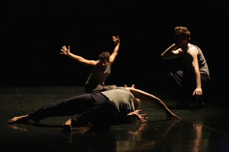 Three dancers in low light in various low lying poses. One dancer in the background splays their arms wide. Another stretches on the floor. The third sits in a crouch.