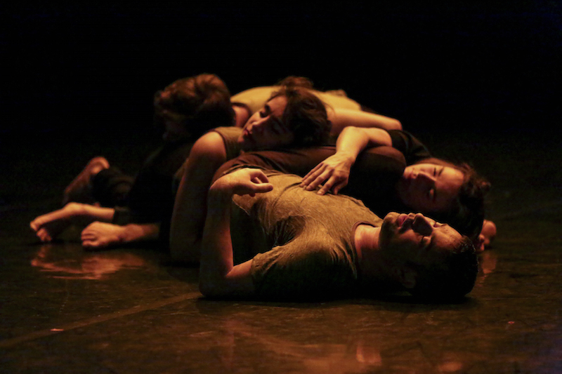 Dancers lay in a heap together. Their limbs tangled and torso draping over one another's.